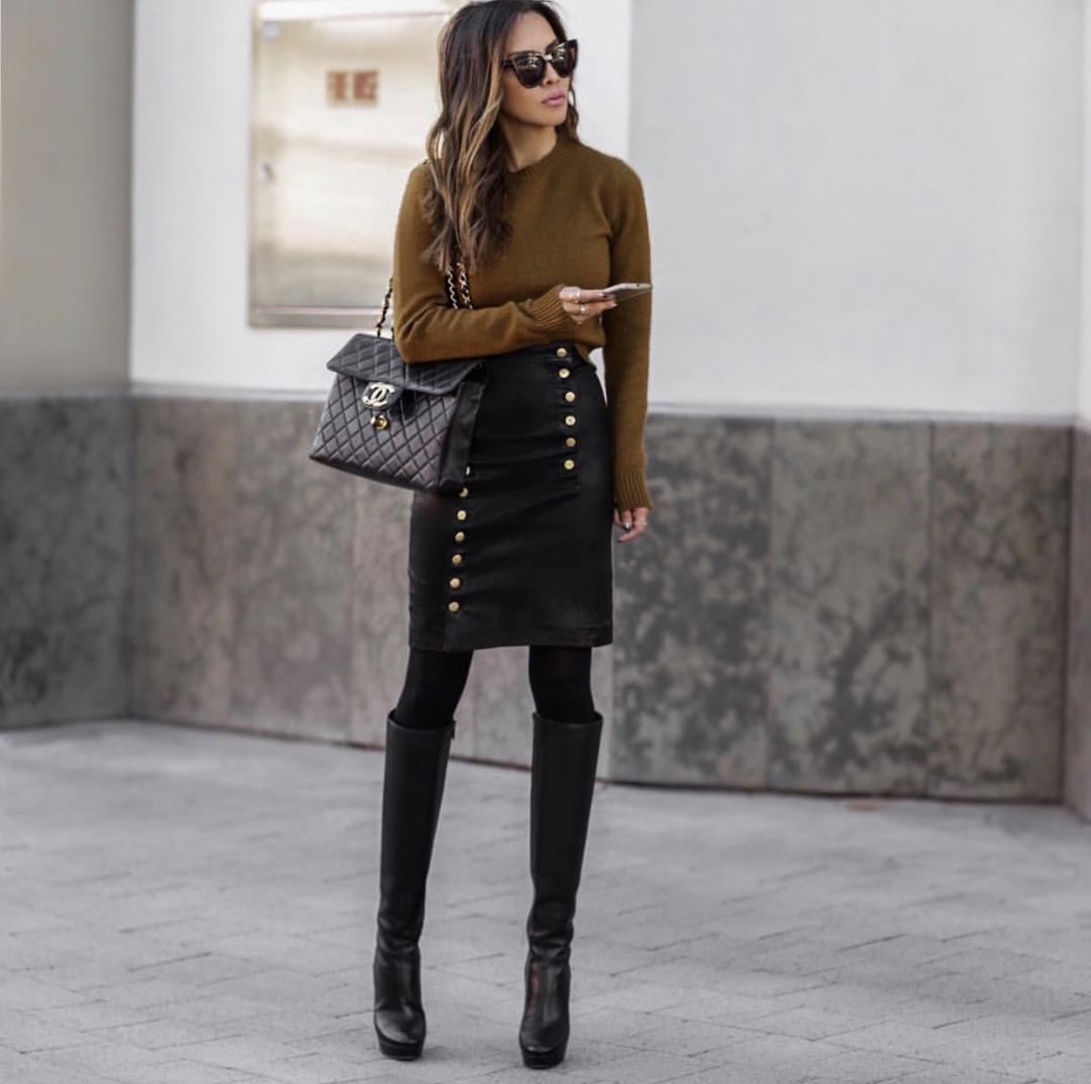 fashion blogger lolario style dresses up in stylish thanksgiving outfits featuring a leather skirt tall leather boots and brown sweater | lolariostyle.com